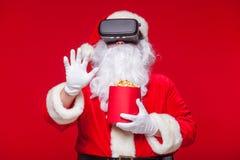 Santa Claus die virtuele werkelijkheidsbeschermende brillen en een rode emmer met popcorn, op een rode achtergrond dragen Kerstmi Royalty-vrije Stock Afbeelding