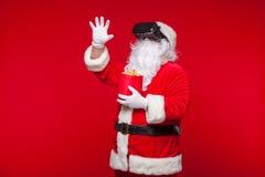 Santa Claus die virtuele werkelijkheidsbeschermende brillen en een rode emmer met popcorn, op een rode achtergrond dragen Kerstmi Royalty-vrije Stock Afbeeldingen