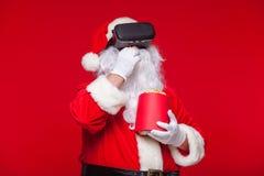 Santa Claus die virtuele werkelijkheidsbeschermende brillen en een rode emmer met popcorn, op een rode achtergrond dragen Kerstmi Stock Afbeeldingen