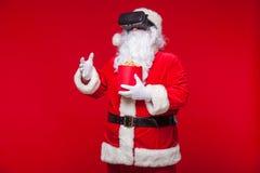 Santa Claus die virtuele werkelijkheidsbeschermende brillen en een rode emmer met popcorn, op een rode achtergrond dragen Kerstmi Royalty-vrije Stock Fotografie