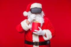 Santa Claus die virtuele werkelijkheidsbeschermende brillen en een rode emmer met popcorn, op een rode achtergrond dragen Kerstmi Stock Foto