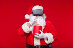 Santa Claus die virtuele werkelijkheidsbeschermende brillen en een rode emmer met popcorn, op een rode achtergrond dragen Kerstmi Royalty-vrije Stock Foto