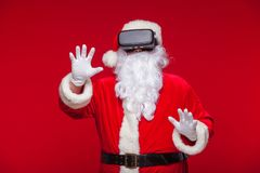 Santa Claus die virtuele werkelijkheidsbeschermende brillen, op een rode achtergrond dragen Kerstmis Royalty-vrije Stock Fotografie