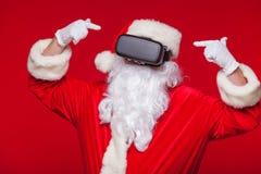 Santa Claus die virtuele werkelijkheidsbeschermende brillen, op een rode achtergrond dragen Kerstmis Stock Foto
