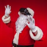 Santa Claus die virtuele werkelijkheidsbeschermende brillen, op een rode achtergrond dragen Kerstmis Royalty-vrije Stock Foto
