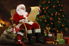 Santa Claus, die vor Kamin sitzt Lizenzfreie Stockbilder