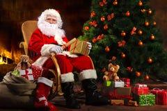 Santa Claus, die vor Kamin sitzt Lizenzfreie Stockfotos