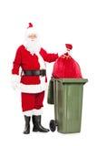 Santa Claus die weg zijn zak werpt van stelt voor Stock Foto