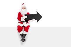 Santa Claus die zwarte pijl houden op een paneel gezet Stock Foto