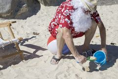 Santa Claus digging in sand with pale and shovel on beach ball Royalty Free Stock Photos
