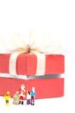 Santa Claus diminuta que está na frente de uma caixa de presente grande Fotografia de Stock Royalty Free
