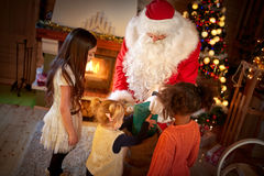 Santa Claus distributes gifts to children Stock Photography