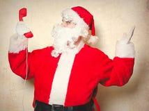 Santa Claus divertente che tiene microtelefono rosso immagini stock