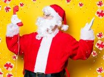 Santa Claus divertente che tiene microtelefono rosso immagine stock libera da diritti