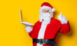 Santa Claus divertente ha un divertimento con il computer portatile Fotografia Stock