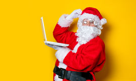 Santa Claus divertente ha un divertimento con il computer portatile Fotografie Stock Libere da Diritti