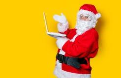 Santa Claus divertente ha un divertimento con il computer portatile Fotografia Stock Libera da Diritti