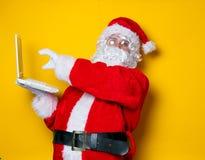 Santa Claus divertente ha un divertimento con il computer portatile Fotografie Stock