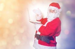 Santa Claus divertente ha un divertimento con il computer portatile Immagine Stock