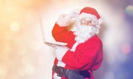 Santa Claus divertente ha un divertimento con il computer portatile Immagini Stock
