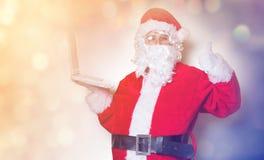 Santa Claus divertente ha un divertimento con il computer portatile Immagini Stock Libere da Diritti