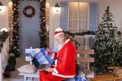 Santa Claus divertida que muestra los pulgares para arriba y que trabaja con el ordenador portátil Fotos de archivo
