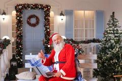 Santa Claus divertida que muestra los pulgares para arriba y que trabaja con el ordenador portátil Fotografía de archivo