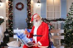 Santa Claus divertida que muestra los pulgares para arriba y que trabaja con el ordenador portátil Fotografía de archivo libre de regalías