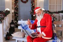 Santa Claus divertida que muestra los pulgares para arriba y que trabaja con el ordenador portátil Imágenes de archivo libres de regalías