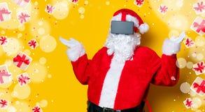 Santa Claus divertida tiene una alegría con los vidrios de VR Foto de archivo libre de regalías