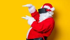 Santa Claus divertida tiene una alegría con los vidrios de VR Imagen de archivo libre de regalías