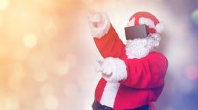 Santa Claus divertida tiene una alegría con los vidrios de VR Fotos de archivo