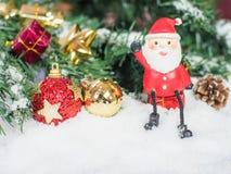 Santa Claus docka och röda och glodjulbollar i snön C Royaltyfria Foton