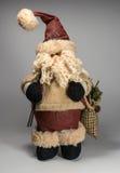 Santa Claus docka som bär en tröja I händerna av skidar hänger löst poler och med gåvor Arkivfoto