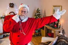 Santa claus doing welcoming gesture while carrying his gift sack Stock Photo