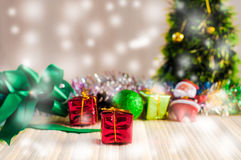 The Santa Claus doll against a Christmas tree with gift box on wood Stock Photos