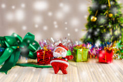 The Santa Claus doll against a Christmas tree with gift box on wood Stock Photo