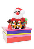 Santa Claus doll on a pile of books. Santa Claus doll and Christmas knickknacks arranged neatly on a pile of books, isolated on white background Stock Images