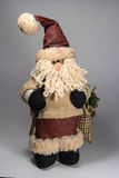 Santa Claus doll wearing a sweater. In the hands of ski poles and bag with gifts. The bag is visible spruce branch. Doll looks right Stock Image