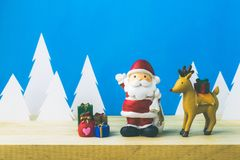 Santa Claus dolls and Christmas decorations box on wooden Royalty Free Stock Photos