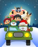 Santa Claus Driving a Green Car Along With Reindeer, Snowman, Children, and Full Moon  Royalty Free Stock Photos