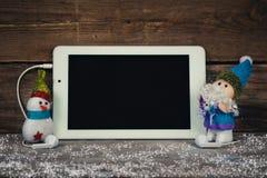 Santa Claus e boneco de neve que guardam a tabuleta Imagem de Stock Royalty Free