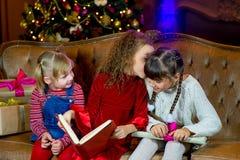 Santa Claus e grupo de meninas que leem um livro Foto de Stock Royalty Free