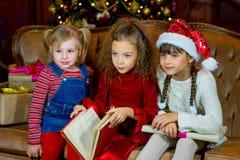 Santa Claus e grupo de meninas que leem um livro Fotografia de Stock Royalty Free