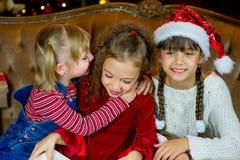 Santa Claus e gruppo di ragazze che leggono un libro Immagine Stock