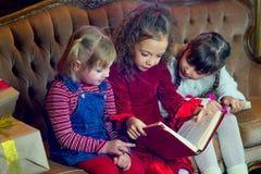Santa Claus e gruppo di ragazze che leggono un libro Immagine Stock Libera da Diritti