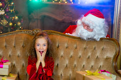 Santa Claus e menina com presentes do Natal Fotos de Stock