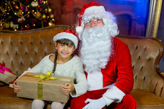 Santa Claus e menina do lettle com presentes do Natal Fotos de Stock Royalty Free
