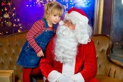 Santa Claus e meninas que leem um livro Imagem de Stock