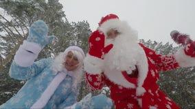 Santa Claus e nipote che ondeggiano le loro mani sulla macchina fotografica nel video di movimento lento della foresta archivi video